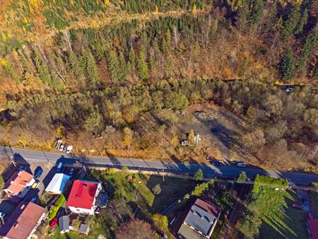 Zdjęcie wykonane z drona przedstawiające drzewa, drogę, domy (kliknięcie spowoduje powiększenie obrazu)