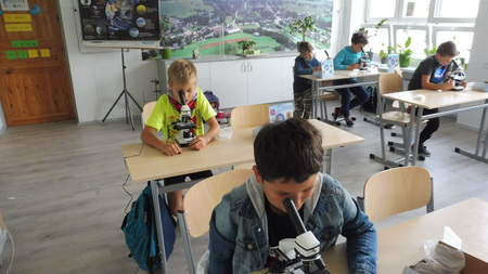 Grupa uczniów korzystająca z mikroskopów w klasopracowni (kliknięcie spowoduje powiększenie obrazu)